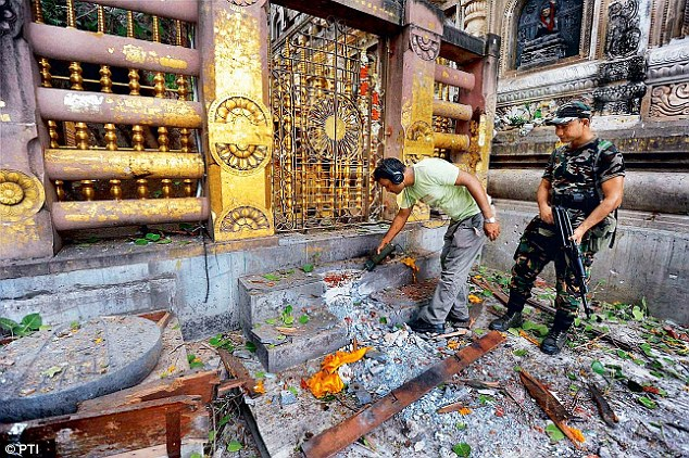 Security personnel inspect the explosion site after a serial blast at the Mahabodhi temple complex in Bodhgaya on Sunday.  (Photo courtesy: PTI)
