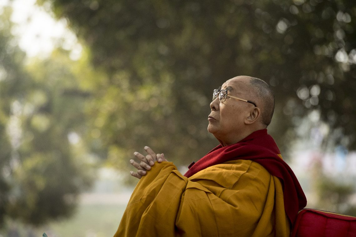 His Holiness the Dalai Lama looking up at the Stupa behind the Bodhi Tree during the prayer session at the Mahabodhi Stupa in Bodhgaya, Bihar, India on January 17, 2018. (Photo courtesy:  Manuel Bauer/OHHDL)