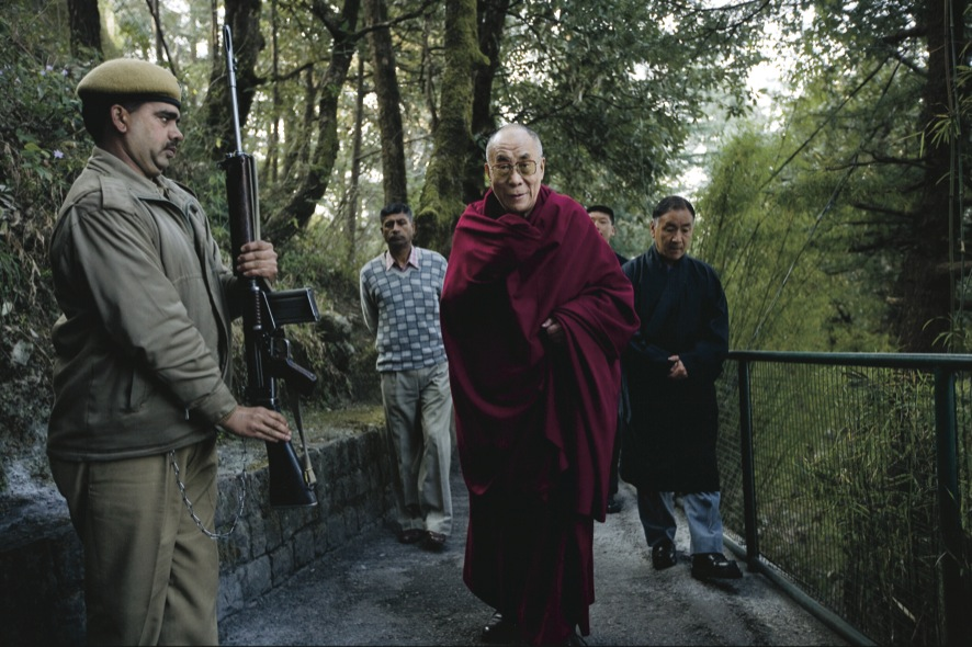 The Dalai Lama walking to his office, guarded by Indian soldiers. (Photo courtesy: OHHDL)