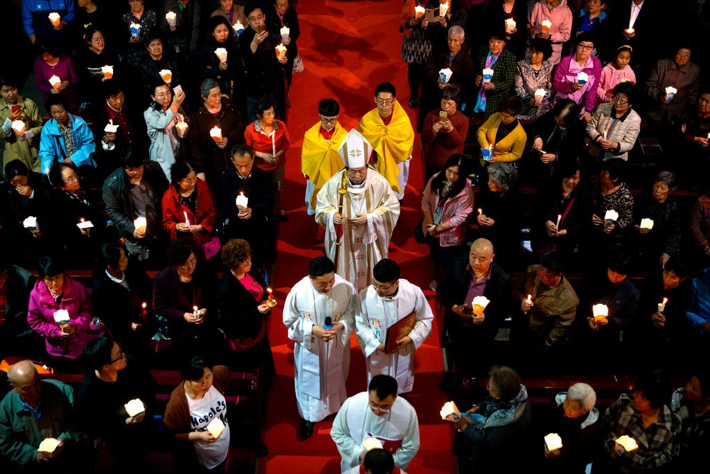 Bishop Joseph Li Shan, center, who was appointed by the Chinese authorities rather than the Vatican, during a Holy Saturday Mass at the Cathedral of the Immaculate Conception, a government-approved church in Beijing. (Photo courtesy: Mark Schiefelbein/AP)