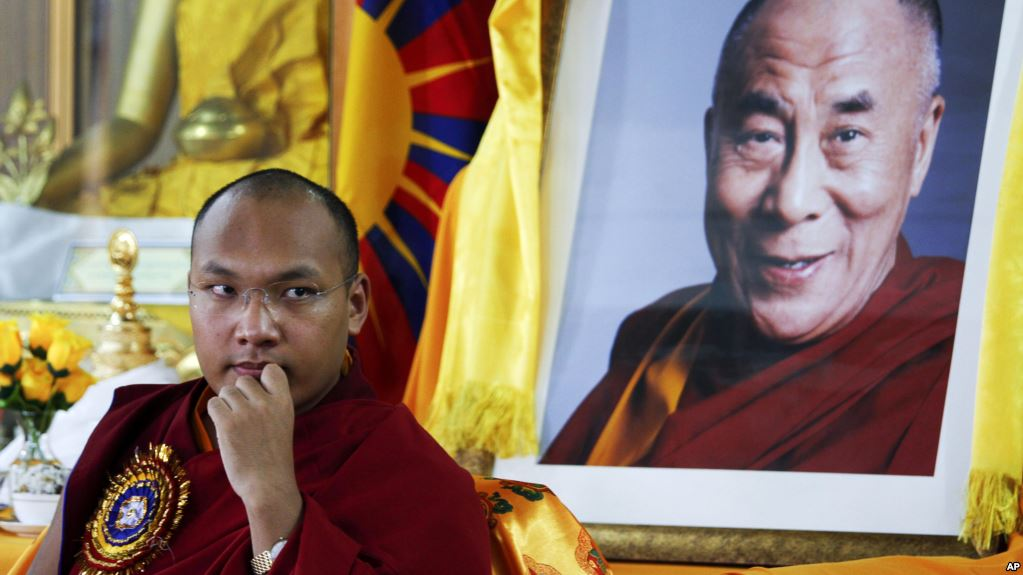 Tibetan spiritual leader Ogyen Trinley Dorje, the 17th Karmapa, looks on as he sits in front of a portrait of the Dalai Lama during a function commemorating the 50th anniversary of the Tibetan Institute of Medicine and Astrology in Dharmsala, India, June 2, 2011. (Photo courtesy: AP)
