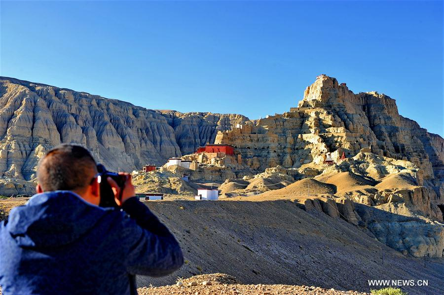 A tourist takes photos of the ruins of the Guge Kingdom in Ngari, Tibet. (Photo courtesy: Xinhua)