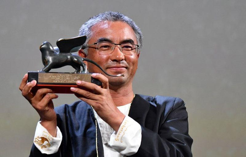 "Director and screenwriter Pema Tseden poses after he received the Orizzonti award for Best Screenplay for the film ""Jinpa"" during the awards ceremony of the 75th Venice Film Festival on Sept 8, 2018 at Venice Lido. (Photo courtesy: LBERTO PIZZOLI / AFP)"