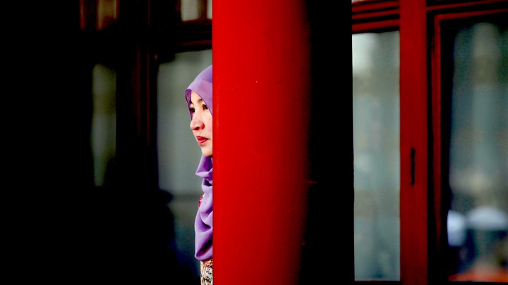 A woman stands behind a pillar during the Eid al-Adha festival at a Chinese mosque. (Photo courtesy: JASON LEE / REUTERS)