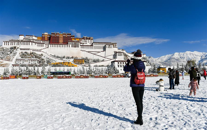 A tourist takes photos at the snow-covered Potala Palace square in Lhasa, capital of Tibet on December 19, 2018. Lhasa witnessed the first snow this winter. (Photo courtesy: Xinhua/Liu Dongjun)
